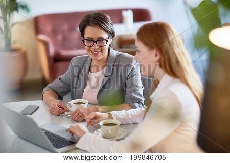 Attractive coworkers gathered together at lovely coffeehouse and discussing joint project with enthusiasm