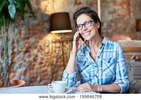 Cheerful attractive woman with stylish haircut talking to her friend on smartphone while enjoying fragrant coffee at lovely cafe
