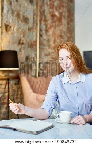 Waist-up portrait of attractive ginger-haired manager looking at camera with charming smile while preparing for important meeting at fashionable cafe
