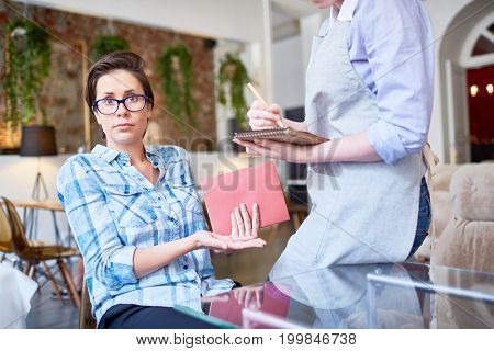 Waist-up portrait of surprised pretty visitor looking at camera and pointing at unskilled waitress sitting on corner of table while writing down order