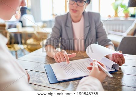 Close-up shot of confident middle-aged entrepreneur pointing her client where to sign contract while having meeting at cozy coffeehouse
