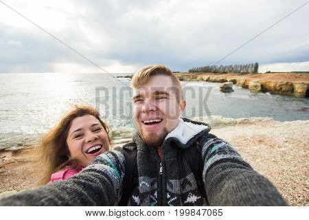Happy young couple in love takes selfie portrait on the beach in Cyprus. Pretty tourists make funny photos for travel blog in Europe