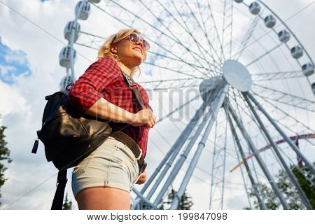Girl in casualwear on backgrounf of ferris wheel spending time in theme park