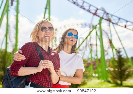 Attractive girls in sunglasses enjoying time in amusement park