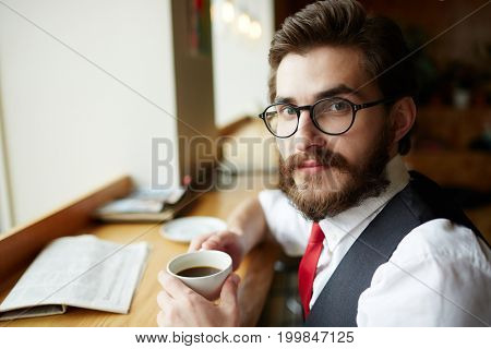 Young specialist or entrepreneur with cup of coffee having break in cafe