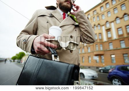 Busy salesman with briefcase and drink talking to client by cellphone