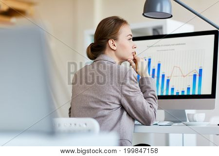 Back view of attractive young white collar worker looking away thoughtfully while analyzing statistic data with help of modern computer, blurred background