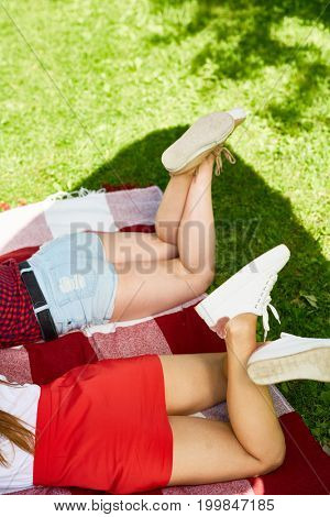 Carefree girls in cross-shoes and casualwear relaxing in shade on sunny day