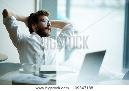 Relaxing businessman sitting in front of laptop and looking through office window