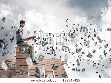 Young man in casual sitting on house with red book in hands