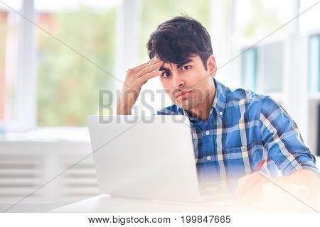 Tense designer or student with laptop looking at camera