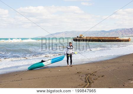 young man carrying his kayak into the water