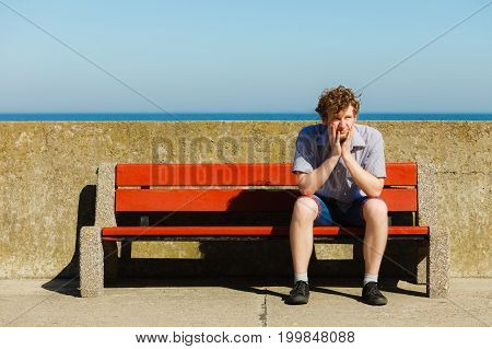 Tired Exhausted Man Sitting On Bench By Sea Ocean.