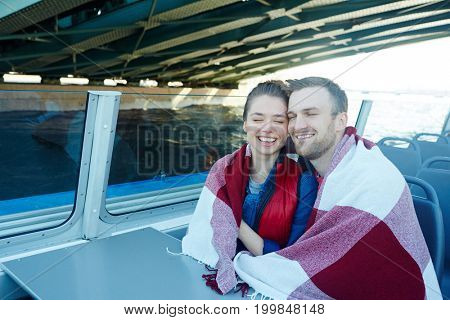 Laughing man and woman wrapped in plaid traveling by motorship