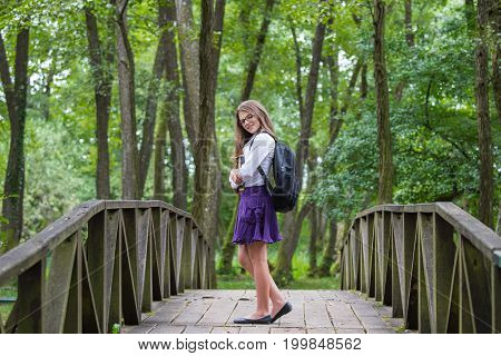 Beautiful Pretty Blonde School Girl Child Smiling With Glasses, White Shirt, Purple Skirt And Black
