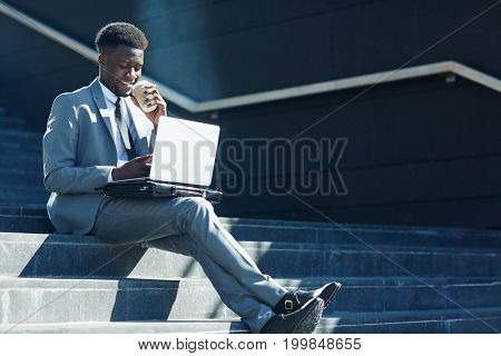 Professional trader having drink while working online on staircase outdoors