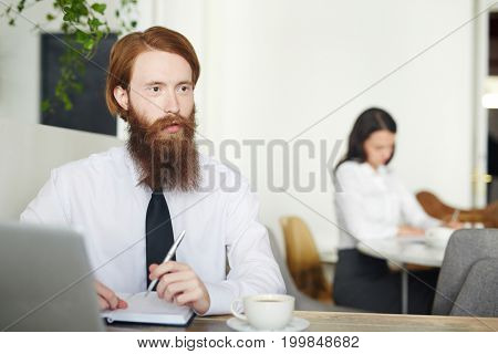 Young specialist or entrepreneur making notes in notebook by cup of tea or coffee in cafe