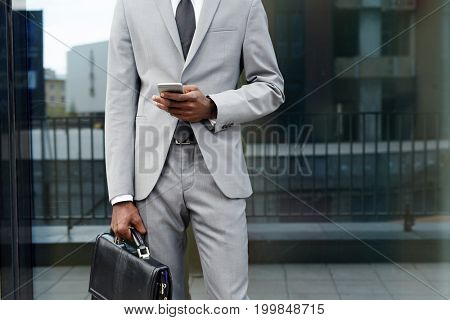 Elegant businessman with briefcase texting in urban environment