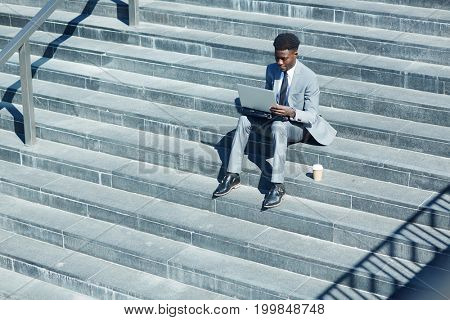 Young stock market trader with laptop networking on staircase in the city