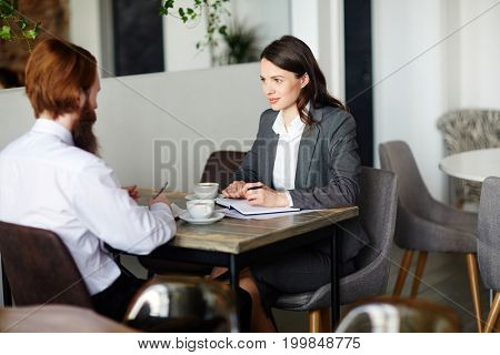 Two young managers having discussion of business project at start-up meeting in cafe