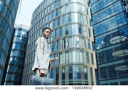 Man in formalwear carrying briefcase and smartphone while walking in urban environment