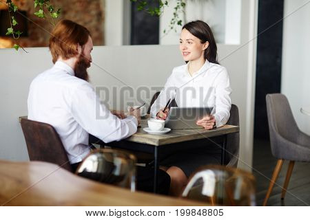 Young businessman and businesswoman interacting at start-up meeting in cafe
