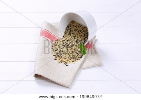 bowl of wild rice spilt out on place mat