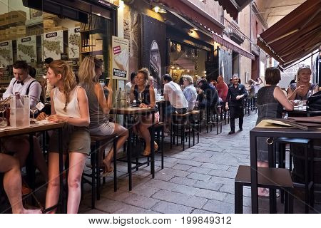 BOLOGNA, ITALY, 16 JUNE 2017 people enjoy an aperitif eating and drinking traditional foods in outdoors bar on a street in the historic center on a hot spring day, 16 June 2017