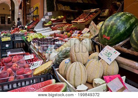 BOLOGNA, ITALY, 16 JUNE 2017 Seasonal fruit and vegetables on the stalls at the open street market in the historic center of bologna with people in the background, 16 June 2017
