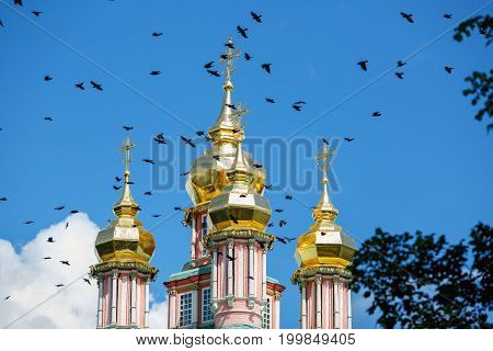 Birds flying over the onion domes of the gate Church of St John The Baptist. Sergiev Posad monastery (Trinity Lavra of St. Sergius), Moscow region, Russia