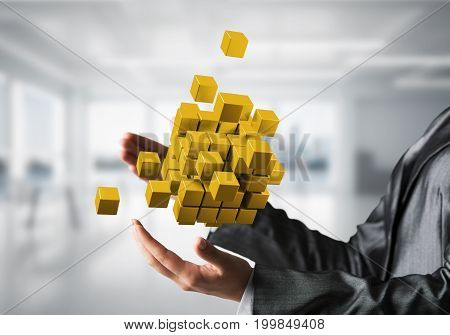 Cropped image of business woman hands holding multiple yellow cubes in hands with office background. Mixed media.