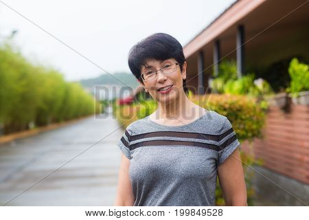 Close-up portrait of beautiful woman standing on the street while looking at camera and smiling.