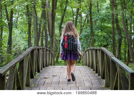 Beautiful Pretty Blonde School Girl Child From Back With White Shirt, Purple Skirt And Backpack Walk