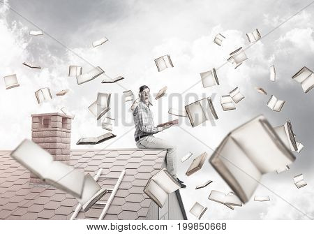 Young smiling man sitting on house roof with red book in hands