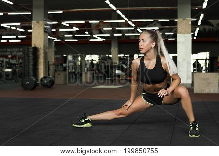 Beautiful young woman do sport exercises. Young woman stretching her legs in gum. Blond sexy girl in gym.