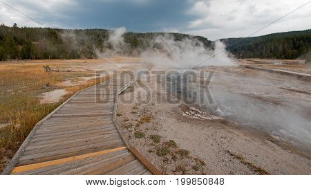 Boardwalk curving around Hot Cascades hot spring in the Lower Geyser Basin in Yellowstone National Park in Wyoming United States