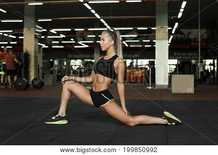 Young blond slim fitness girl standing in modern gym preparing for workout attractive professional trainer dressed in sports outfit making warming up exercises before starting pilates