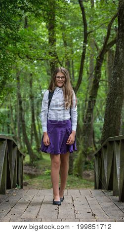 Beautiful Pretty Blonde School Girl Child Smiling With Glasses, White Shirt, Purple Skirt And Backpa