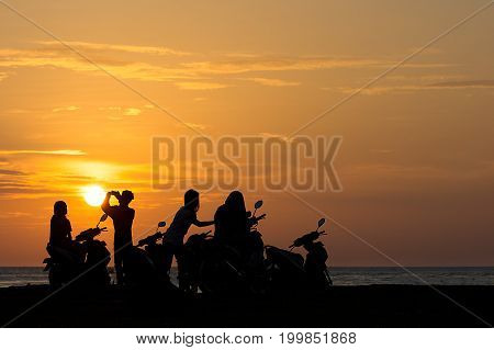 Group Gang of Teenagers Young Adults watch a beach side sun set on their scooters.