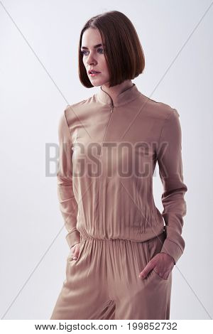 Side view of chestnut woman posing having hands in pockets in studio