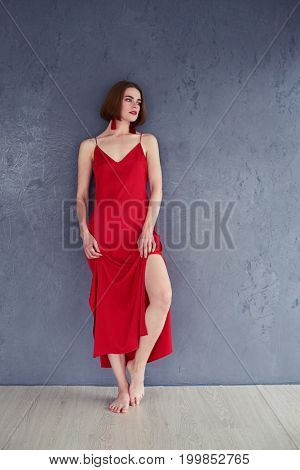Vertical of romantic female posing in red dress on grey background with copy space