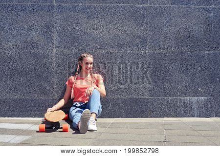 Wide shot of gorgeous female while sitting under wall with skateboard with copy space