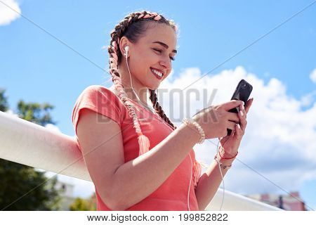 Low angle of graceful blonde in headset surfing in smartphone
