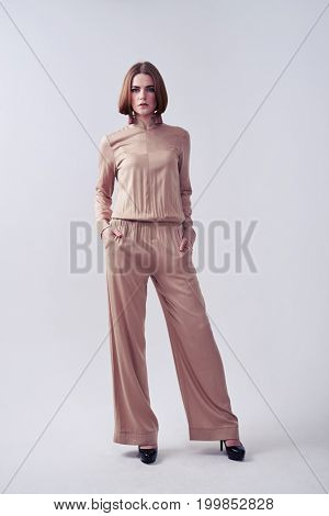 Vertical of stylish lady posing in beige overalls in studio with copy space