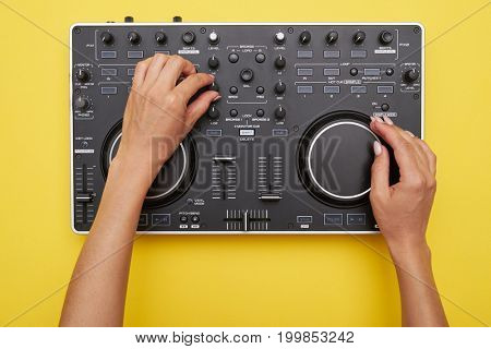 Flat lay of mixing board on yellow background. View of hands of woman using electronic device, mid shot