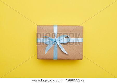 Flat lay of romantic gift decorated with blue ribbon on yellow background