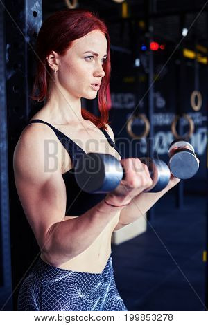 Side view of happy determined woman working out with dumbbells at home