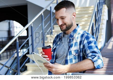 Close-up shot of man with beard using tablet and listening music. Standing next to window, holding paper cup with coffee