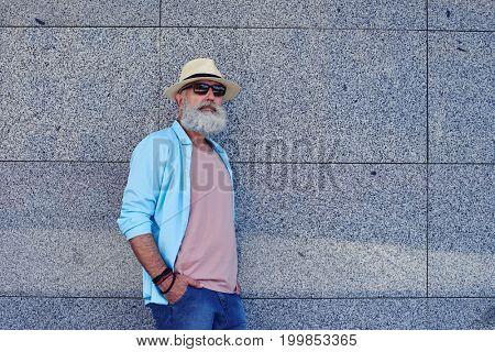 Mid shot of grey bearded man in sunglasses, having stylish clothing, warm sunny day outdoors