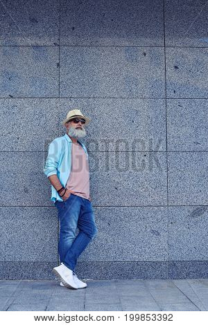 Full-length portrait of man with grey beard in stylish clothing, wearing sunglasses and sneakers, mid shot